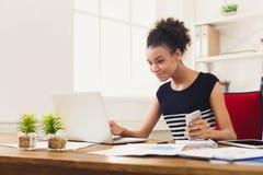 研究膝上型计算机的愉快的女商人在办公室 免版税库存图片