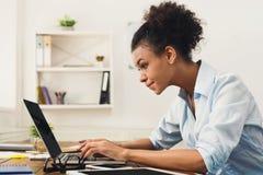 研究膝上型计算机的愉快的女商人在办公室 库存图片