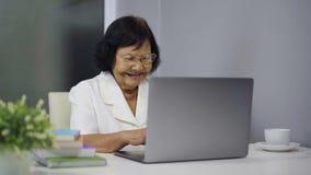 研究膝上型计算机的愉快的资深妇女 股票录像