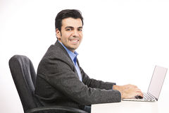 研究膝上型计算机的愉快的年轻商人 免版税库存图片