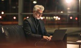 研究膝上型计算机的成熟商人在办公室 库存图片