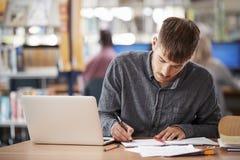 研究膝上型计算机的成熟男学生在大学图书馆里 免版税库存照片