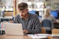 研究膝上型计算机的成熟男学生在大学图书馆里 图库摄影