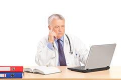 研究膝上型计算机的成熟医生在他的书桌 免版税库存照片