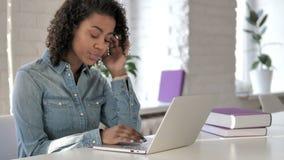 研究膝上型计算机的打呵欠的疲乏的创造性的非洲女孩 股票录像