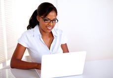 研究膝上型计算机的新俏丽的女实业家 免版税库存图片