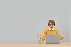 研究膝上型计算机的时髦妇女是非常繁忙的 图库摄影