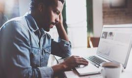研究膝上型计算机的有胡子的非洲人,当在家时花费时间 使用移动设备的年轻商人的概念 免版税库存图片