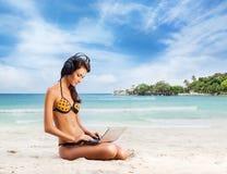 研究膝上型计算机的泳装的性感的妇女 免版税库存照片