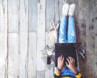 研究膝上型计算机的牛仔裤的女孩计算机辅助由她的在木地板上的猫 库存图片