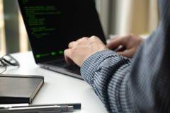 研究膝上型计算机的程序员在办公室 在编程的代码的焦点 库存照片