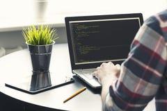 研究膝上型计算机的程序员在办公室 免版税库存图片