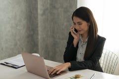 研究膝上型计算机的美丽的亚裔年轻女实业家,当是s时 库存照片