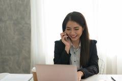 研究膝上型计算机的美丽的亚裔年轻女实业家,当是s时 图库摄影