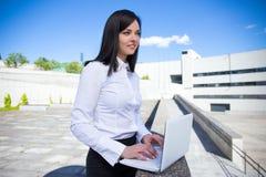 研究膝上型计算机的美丽的女商人在办公室外 免版税图库摄影