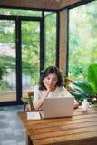研究膝上型计算机的美丽的年轻微笑的妇女在大窗口附近 免版税库存图片