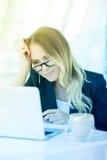 研究膝上型计算机的美丽的年轻办公室妇女画象在  免版税库存图片
