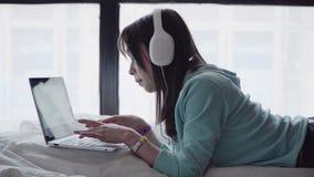 研究膝上型计算机的耳机的妇女 股票录像