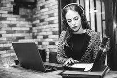 研究膝上型计算机的耳机的年轻女实业家 免版税库存图片