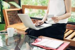 研究膝上型计算机的聪明的便衣的确信的年轻亚裔妇女,当坐在创造性的办公室或咖啡馆时的窗口附近 库存图片