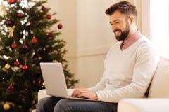 研究膝上型计算机的英俊的人在有圣诞树的屋子里 免版税库存图片