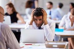 研究膝上型计算机的被注重的商人在繁忙的办公室 免版税库存图片