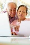 研究膝上型计算机的资深台湾夫妇 免版税库存照片