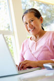 研究膝上型计算机的资深台湾妇女 免版税库存照片