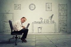 研究膝上型计算机的资深商人执行委员在办公室 免版税图库摄影