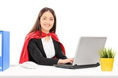 研究膝上型计算机的超级英雄服装的妇女 免版税图库摄影