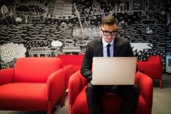 研究膝上型计算机的镜片的人,当坐在现代办公室时 免版税库存图片