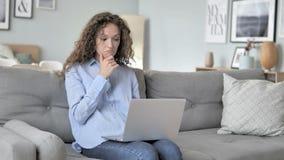 研究膝上型计算机的震惊卷发妇女,坐长沙发