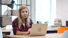 研究膝上型计算机的黑人妇女,微笑往照相机 股票录像