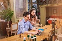研究膝上型计算机的年轻夫妇坐在厨房里 库存图片