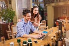 研究膝上型计算机的年轻夫妇坐在厨房里 库存照片