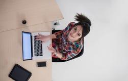 研究膝上型计算机的年轻女商人顶视图  免版税库存图片