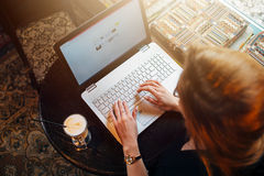 研究膝上型计算机的年轻女学生顶视图坐在桌上 免版税库存照片