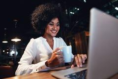 研究膝上型计算机的年轻女实业家在夜间 免版税库存照片