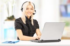 研究膝上型计算机的年轻女性顾客服务操作员 免版税库存图片