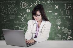研究膝上型计算机的医生在实验室 免版税库存图片