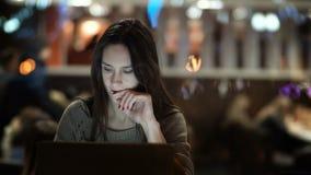 研究膝上型计算机的年轻美丽的妇女在晚上 在咖啡馆的深色的女性开会和谈话在智能手机 影视素材
