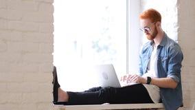 研究膝上型计算机,坐放松输入窗口的人 免版税库存图片