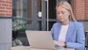 研究膝上型计算机,坐的年轻女实业家室外