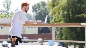 研究膝上型计算机,键入的年轻人,站立在室外的阳台上 免版税库存图片