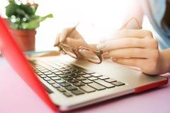研究计算机在办公室和拿着玻璃的妇女 免版税库存照片
