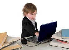 研究计算机的一个小的小女孩(男孩)。 库存图片