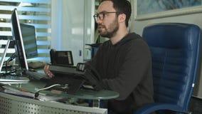 研究计算机的一个男性办公室工作者的侧视图在一个明亮的办公室 免版税库存图片