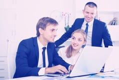 研究计算机的三个苍劲的工友在公司办公室 免版税库存图片
