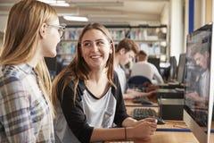 研究计算机的两个女学生在大学图书馆里 图库摄影