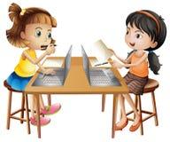 研究计算机的两个女孩 免版税库存照片